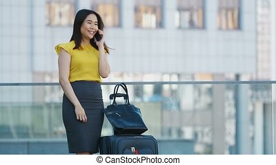 Asian business woman talking on cellphone outdoors