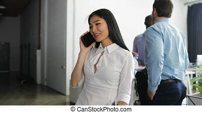 Asian Business Woman Talking On Phone Call Holding Documents In Modern Creative Office Beautiful Businesswoman Working