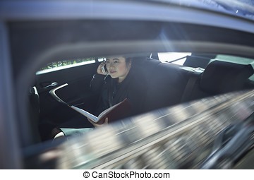 Asian business woman working in back of a car - Chinese...