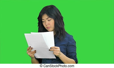 Asian business women looking document file in her hand on a Green Screen, Chroma Key