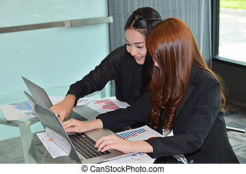 Asian business women using laptops in meeting room