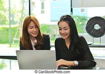 Asian business women working and using laptop in meeting room