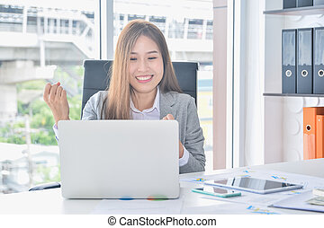 Asian business working with laptop and having success raising arms after get good news