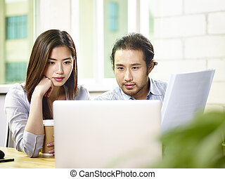 asian businessman and businesswoman working together in office using laptop computer