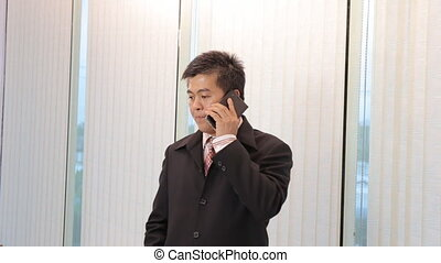 Businessman calling mobile phone - Asian Businessman calling...