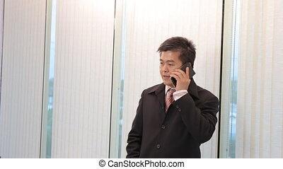 Asian Businessman calling mobile phone