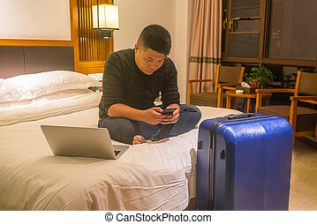 Asian businessman checking email on phone in the hotel room