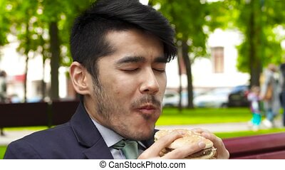 Asian businessman eating tasty burger sitting in the summer...