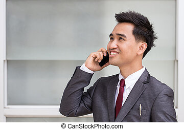 Asian businessman in suit speaking on the phone