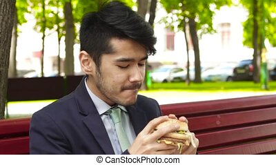 Asian businessman is sitting on bench in park and eating big...