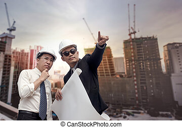 Asian businessman looking and point to finger away and engineer architect hold construction industrial plan background for working together as team concept