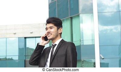 Asian businessman making phone calls and dancing winner...