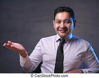 Asian Businessman Presenting Something on His Side with Copy Space