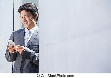 Asian businessman sending text message