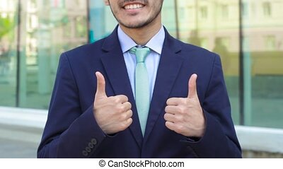 Asian businessman show double thumbs up using two hands