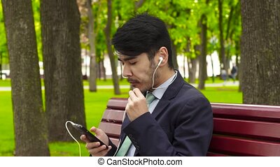 Asian businessman sitting in park and eating french fry in...