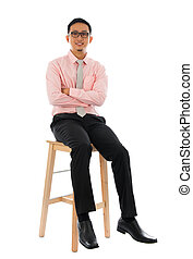 Asian businessman sitting on a wooden chair