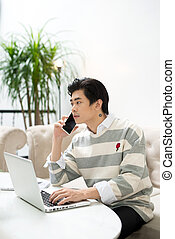 Asian businessman using mobile phone while working with laptop on table in coffee shop