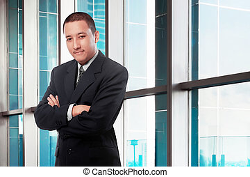 Asian businessman with arms crossed standing in office
