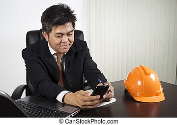 Asian businessman working and holding smrt phone