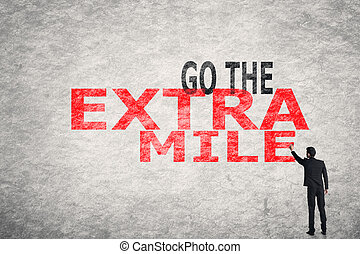 text on wall, Go To Extra Mile - Asian businessman write ...