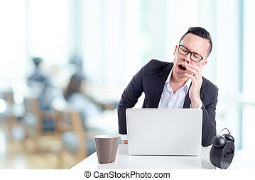 Asian businessman yawning between working in office