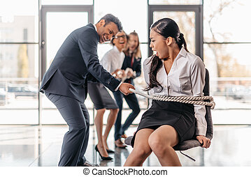 asian businesswoman bound with rope on chair and...