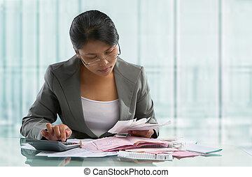 Asian businesswoman calculating bills