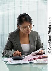 Asian businesswoman checking bills