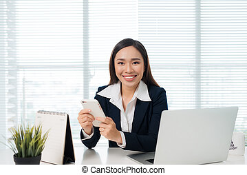 Asian businesswoman holding smartphone while sitting at her desk