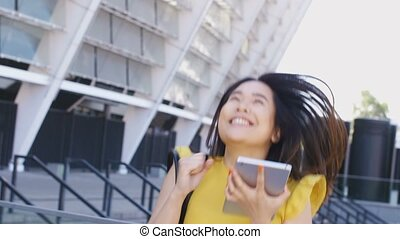 Asian businesswoman jumping happy with touchpad