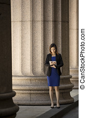 Asian businesswoman outside Colonial building using tablet.