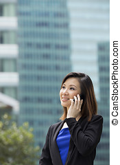 Asian businesswoman outside in modern city using Phone.