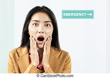 Asian businesswoman shocked in front of the emergency room