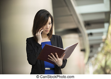 Asian businesswoman standing outside using phone
