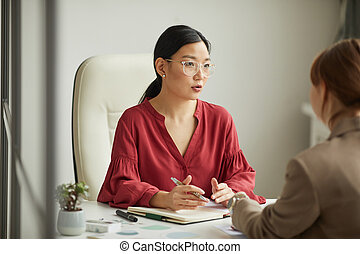 Asian Businesswoman Talking to Client in Office
