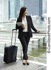 Asian Businesswoman using digital tablet with suitcase