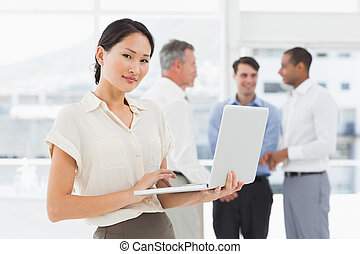 Asian businesswoman using laptop with team behind her