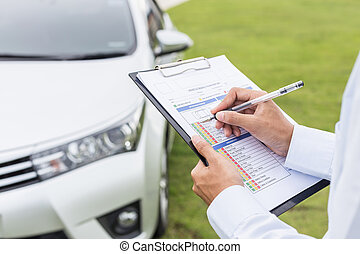 Asian car technician holding checklist paper in front of the car. For car repair concept