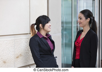 Asian & Caucasian businesswomen having chat. - Two...