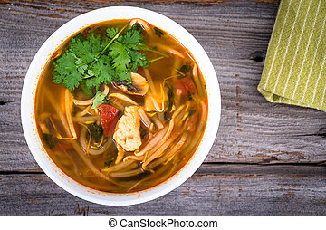 asian chicken tomyum soup bowl on table closeup