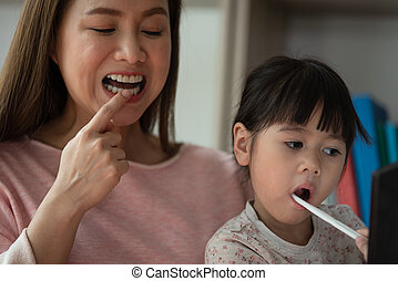 Asian child brushing teeth with mother in bathroom
