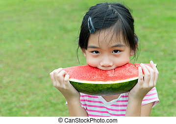 Asian child eating watermelon