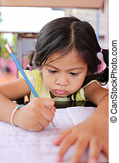 Asian child girl use Pencil write letters on the book.