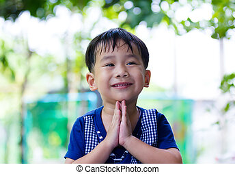 Asian child put the palms of the hands together in salute.