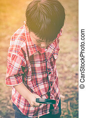 Asian child with magnifying glass at park on vacation. Education concept. Warm tone.