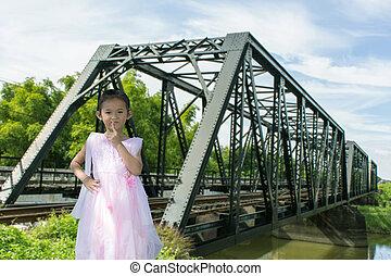 Asian children girl old iron railway construction bridge in Lamphun Thailand