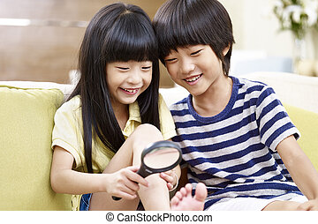 asian children having fun with a magnifier