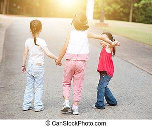 Asian children holding hands walking outdoor.