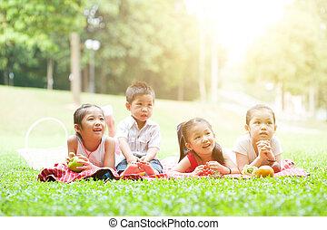 Asian children picnics outdoor.